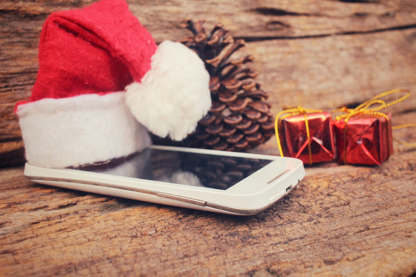 Smart phone and gift with christmas hat